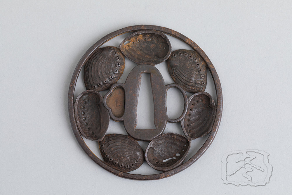 IRON TSUBA 18th/ 19th Century An iron tsuba decorated with seven finely worked abalone shells. With fitted wood box. Unsigned Diametre: 8cm